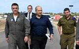 Defense Minister Naftali Bennett, center, and Air Force commander Maj. Gen. Amikam Norkin, left, during a visit to the Hatzor Air Force Base on December 3, 2019. (Twitter screen capture)