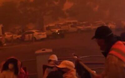 People preparing to evacuate as fires hem in the city of Mallacoota, Victoria, Australia. (screen capture: YouTube)