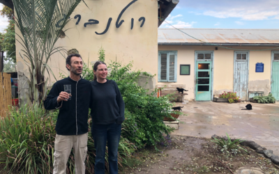 Yizhar Sahar (left) and Hila Ronen Sahar, in front of Rutenberg, their Jordan Valley farm-to-table bistro on the border between Israel and Jordan (Jessica Steinberg/Times of Israel)