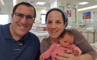 Tzippi Rimel (R) with her husband Ephraim and three-week-old daughter Noam. (Courtesy)