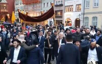 Jewish revelers dance down the street formerly named after Adolf Hitler in Freiburg im Breisgau in Germany as they welcome a Torah in December 2019 (Screencapture/YouTube)