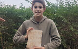 Stav Meir, 13, holding a 1,500-year-old Greek burial inscription that he discovered near Caesarea. (Karem Said/ Israel Antiquities Authority)