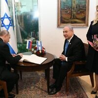 Russian President Vladimir Putin (L) signs the guest book at the Prime Minister's Residence, with Prime Minister Benjamin Netanyahu (C) and his wife, Sara (R), Jerusalem, 23 January, 2020 (Amos Ben Gershon/GPO)