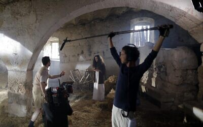 Members of a film crew shoot a scene on the set of an Israeli television series inside the Beit Jamal monastery, near the central city of Bet Shemesh, west of Jerusalem, on December 11, 2019. (AHMAD GHARABLI / AFP)