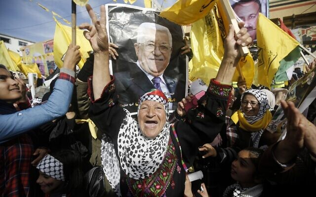 Supporters of the Palestinian Fatah movement, carry the portrait of Fatah chairman and Palestinian Authority President Mahmoud Abbas, during a rally marking the 55th foundation anniversary of the political party, in Gaza City on January 1, 2020. (Mohammed Abed/AFP)