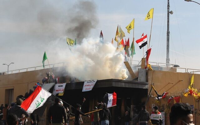 US forces (unseen) fire teargas canisters at supporters and members of the Hashed al-Shaabi paramilitary force during a demonstration outside the US embassy in the Iraqi capital Baghdad on January 1, 2020.  (AHMAD AL-RUBAYE / AFP)