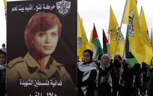 Supporters of the Palestinian Fatah movement march with a poster of female terrorist Dalal al-Mughrabi, who took part in the 1978 Coastal Road massacre in Israel, during a rally marking the 55th foundation anniversary of the political party in the West Bank town of Bethlehem on January 1, 2020. (Musa AL SHAER / AFP)