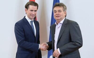 Head of the Austrian People's Party (OeVP) Sebastian Kurz (L) and head of the Green Party Werner Kogler (R) shake hands during a media statement in Vienna on January 01, 2020. (ALEX HALADA / AFP)