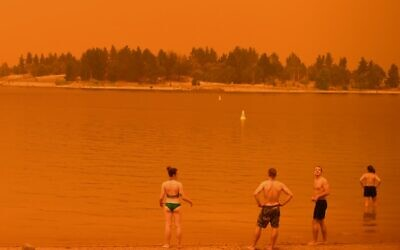 Residents take a dip to cool down at Lake Jindabyne, under a red sky due to smoke from bushfires, in the town of Jindabyne in New South Wales on January 4, 2020 (Saeed KHAN / AFP)