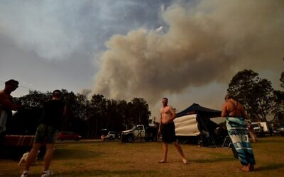 People take shelter by the beach as a bushfire burns in Batemans Bay in New South Wales on January 4, 2020 (PETER PARKS / AFP)