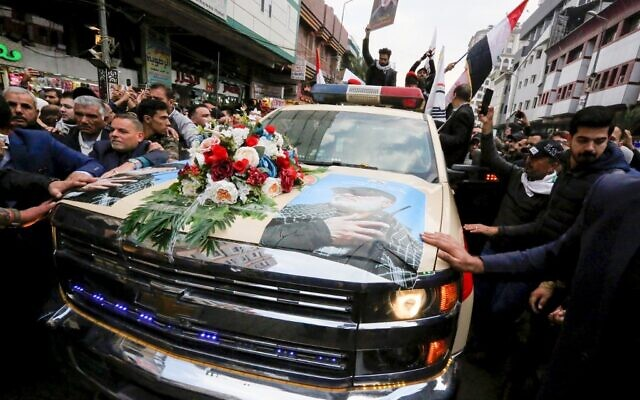 Mourners surround a car carrying the coffin of Iranian military commander Qassem Soleimani, killed alongside Iraqi paramilitary chief Abu Mahdi al-Muhandis in a US air strike, during a funeral procession in Kadhimiya, a Shiite pilgrimage district of Baghdad, on January 4, 2020 (SABAH ARAR / AFP)