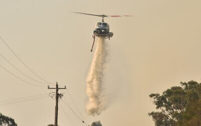 A helicopter drops water on a bushfire in Batemans Bay in New South Wales on January 4, 2020 (PETER PARKS / AFP)