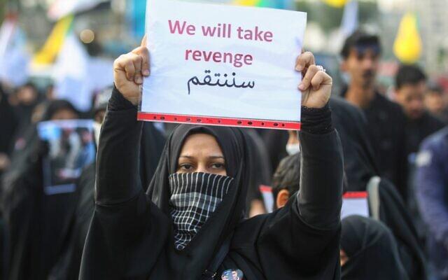 An Iraqi woman holds a placard during the funeral of Iranian military commander Qasem Soleimani, Iraqi paramilitary chief Abu Mahdi al-Muhandis and eight others in Baghdad's district of al-Jadriya on January 4, 2020. (AHMAD AL-RUBAYE / AFP)