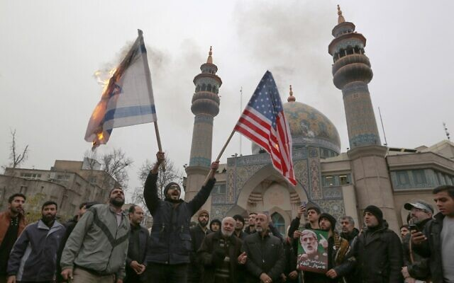 Iranians burn an Israeli and a US flag during an anti-US protest in the capital Tehran on January 4, 2020, over the killings during a US airstrike of Iranian military commander Qasem Soleimani and Iraqi paramilitary chief Abu Mahdi al-Muhandis. (Atta Kenare/AFP)