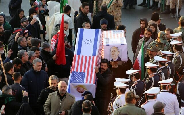 Mourners carry mock coffins with images of US President Donald Trump and Israeli Prime Minister Benjamin Netanyahu pasted on them as they gather to pay homage to slain Iranian military commander Qassem Soleimani, Iraqi paramilitary chief Abu Mahdi al-Muhandis and other targets of a US attack, in the capital Tehran on January 6, 2020. (Photo by Atta KENARE / AFP)