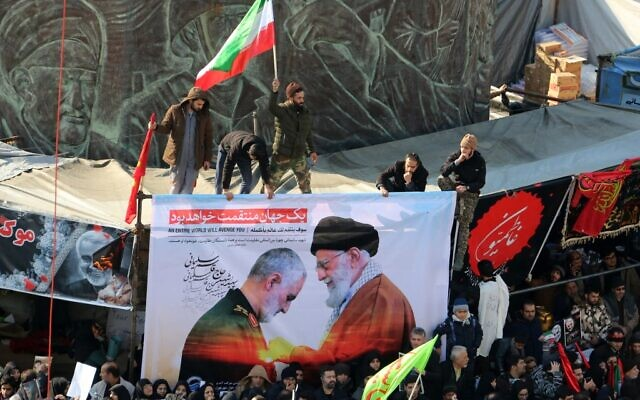 Iranian mourners carry a picture of Iran's Supreme Leader Ayatollah Ali Khamenei (R) granting the Order of Zolfaghar, the highest military honor of Iran, to general Qassem Soleimani, during the latter's funeral procession in the capital Tehran on January 6, 2020. (ATTA KENARE/AFP)