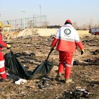 Rescue teams recover a body after a Ukrainian plane carrying 176 passengers crashed near Imam Khomeini airport in the Iranian capital Tehran on January 8, 2020, killing everyone on board. (AFP)
