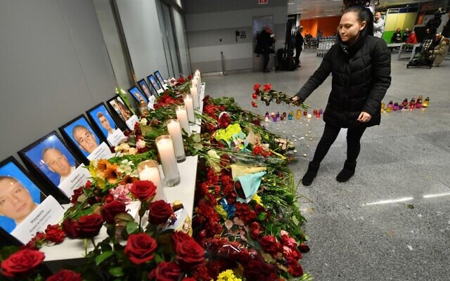 A woman places flowers at a memorial for the victims of the Ukraine International Airlines Boeing 737-800 crash in the Iranian capital Tehran, at the Boryspil airport outside Kiev on January 8, 2020 (Sergei SUPINSKY / AFP)