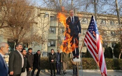 Members of the Basij, a militia loyal to the Islamic republic's establishment, burn a cardboard cutout of Britain's ambassador Rob Macaire alongside a Union Jack and US flag during a memorial for victims of the Ukraine plane crash, at University of Tehran on January 14, 2020. (ATTA KENARE / AFP)