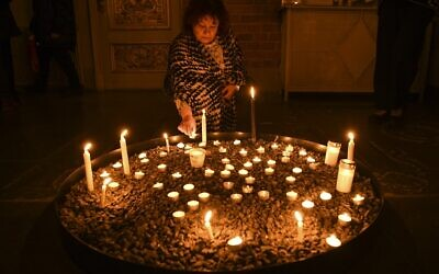 A mourner lights a candle at a memorial service for the victims of Ukrainian Airlines flight PS752 crash in Iran at Storkyrkan church in Stockholm on January 15, 2020. (Jonathan NACKSTRAND / AFP)