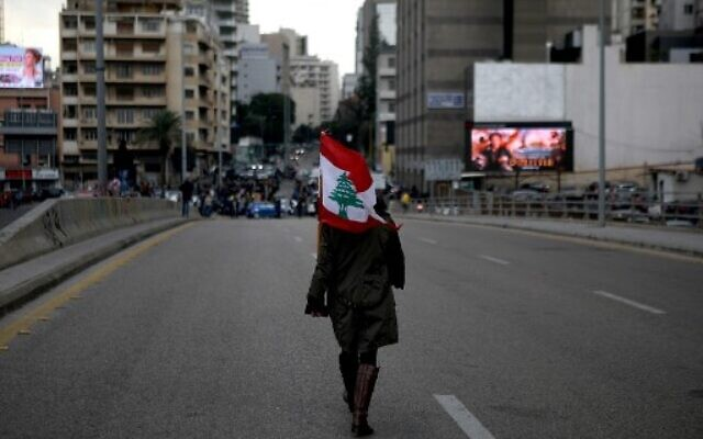 A woman carrying a national flag walks toward Lebanese demonstrators blocking the main bridge linking the western and eastern sides of the capital Beirut, to protest against a political elite accused of corruption and incompetence, on Janury 17, 2020.  (Photo by PATRICK BAZ / AFP)