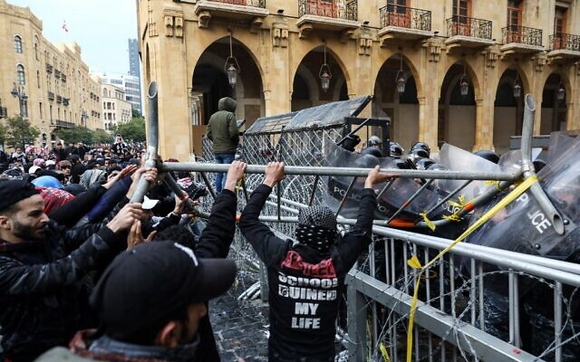 Anti-government protesters use a metal barrier to ram security forces taking cover during clashes in the central downtown district of the Lebanese capital Beirut near the parliament headquarters on January 18, 2020. (ANWAR AMRO / AFP)