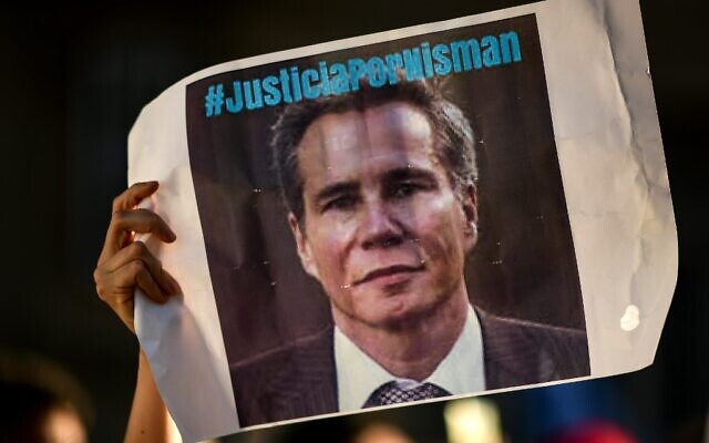 People hold signs during the commemoration of the fifth anniversary of the death of the special prosecutor in the AMIA case, Alberto Nisman, on January 18, 2020, in Buenos Aires. (RONALDO SCHEMIDT/AFP)