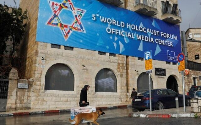 An Israeli man walks with his dog by a hanging poster of the World Holocaust Forum in Jerusalem on January 22, 2020 - World leaders are to travel to Israel this week to mark 75 years since the Red Army liberated Auschwitz, the extermination camp where the Nazis killed over a million Jews. (Photo by AHMAD GHARABLI / AFP)