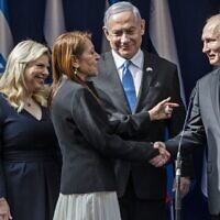 Prime Minister Benjamin Netanyahu, center, smile as Yaffa Issachar, second left, the mother of Naama Issachar, who is imprisoned in Russia, shakes hands with Russian President Vladimir Putin, right, in Jerusalem on January 23, 2020, ahead of the World Holocaust Forum. (Heidi Levine/Pool/AFP)