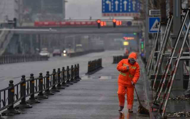A worker wearing a protective facemask sweeps a street in Wuhan on January 25, 2020 (Hector RETAMAL / AFP)