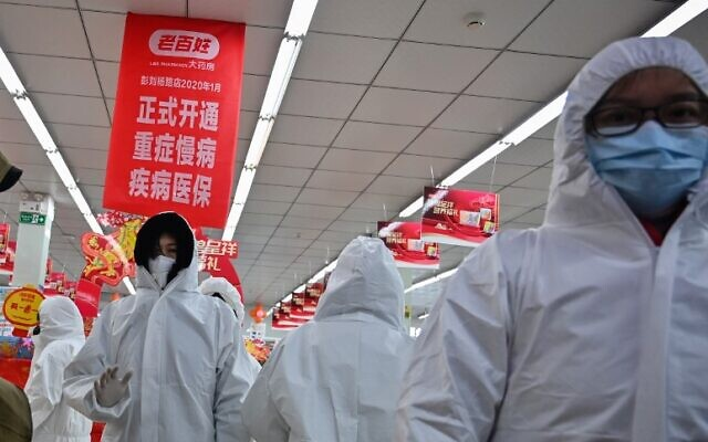 Pharmacy workers wearing protective clothes and masks serve customers in Wuhan on January 25, 2020 (Hector RETAMAL / AFP)
