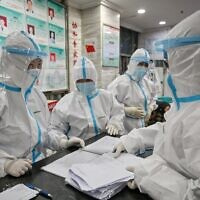 Medical staff wearing protective clothing to help stop the spread of a deadly virus which began in the city, work at the Wuhan Red Cross Hospital in Wuhan on January 25, 2020. (Hector RETAMAL / AFP)