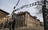 """Holocaust survivor and former prisoner of the Nazi death camp Auschwitz-Birkenau, Johnny (Ephroim) Jablon, left, crosses the gate with the inscription reading """"Work sets you free"""" (Arbeit macht frei) in Oswiecim on January 26, 2020, one day before the 75th anniversary of its liberation. (Wojtek Radwanski/AFP)"""