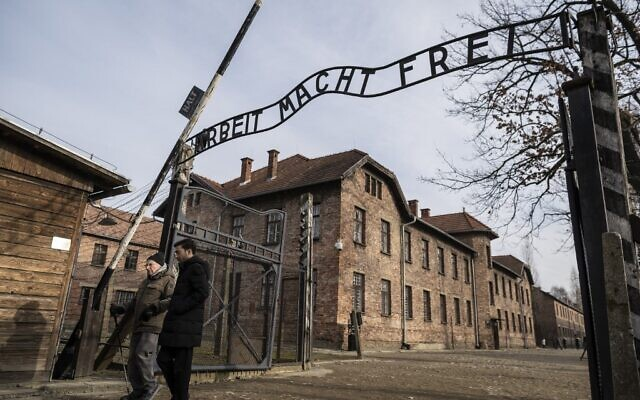 "Holocaust survivor and former prisoner of the Nazi death camp Auschwitz-Birkenau, Johnny (Ephroim) Jablon, left, crosses the gate with the inscription reading ""Work sets you free"" (Arbeit macht frei) in Oswiecim on January 26, 2020, one day before the 75th anniversary of its liberation. (Wojtek Radwanski/AFP)"
