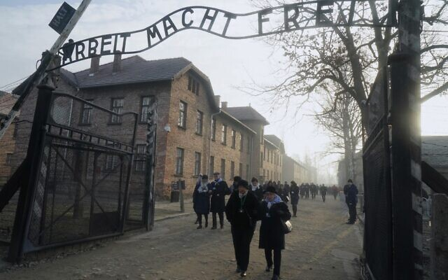 "Holocaust survivors walk below the gate with its inscription ""Work sets you free"" after a wreath laying at the death wall at the memorial site of the former Nazi death camp Auschwitz during ceremonies to commemorate the 75th anniversary of the camp's liberation in Oswiecim, Poland, on January 27, 2020 (JANEK SKARZYNSKI / AFP)"