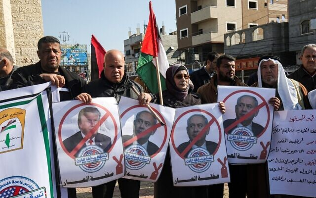 Palestinian demonstrators chant slogans while holding portraits of US President Donald Trump and Prime Minister Benjamin Netanyahu, during a protest against Trump's expected announcement of a peace plan, in Rafah in the southern Gaza Strip on January 28, 2020. (Photo by SAID KHATIB / AFP)