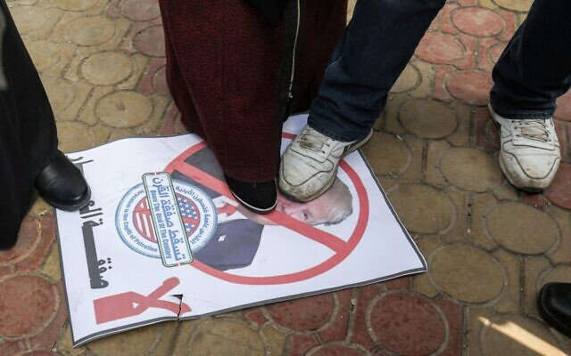 Palestinian demonstrators step with their feet on a poster showing the face of US President Donald Trump during a protest against his expected announcement of a peace plan, in Rafah in the southern Gaza Strip on January 28, 2020. (Photo by SAID KHATIB / AFP)