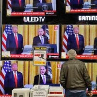 An Israeli man watches the televised press conference of US President Donald Trump and Prime Minister Benjamin Netanyahu at an electronics shop in the Israeli city of Modiin on January 28, 2020. (Gil Cohen-Magen/AFP)