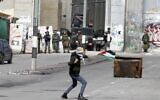 A Palestinian rioter hurls a rock during clashes with Israeli security forces following a protest in the West Bank city of Bethlehem on January 29, 2020. (Musa AL SHAER / AFP)