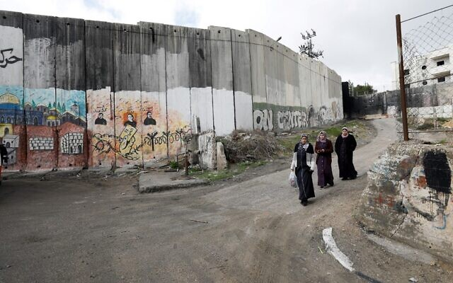 Women walk along Israel's controversial wall dividing east Jerusalem from the Palestinian village of Abu Dis, the proposed Palestinian capital in US President Donald Trump plan for the Middle East, on January 29, 2020. (EMMANUEL DUNAND / AFP)