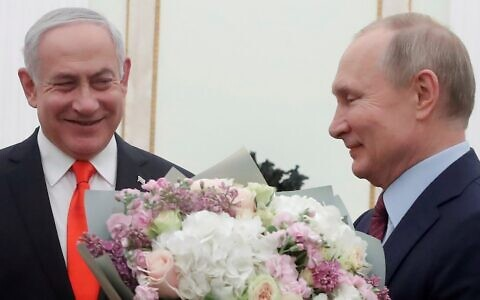 Russian President Vladimir Putin (right) with a bouquet of flowers and Prime Minister Benjamin Netanyahu at the Kremlin in Moscow on January 30, 2020. (Maxim Shemetov/Pool/AFP)