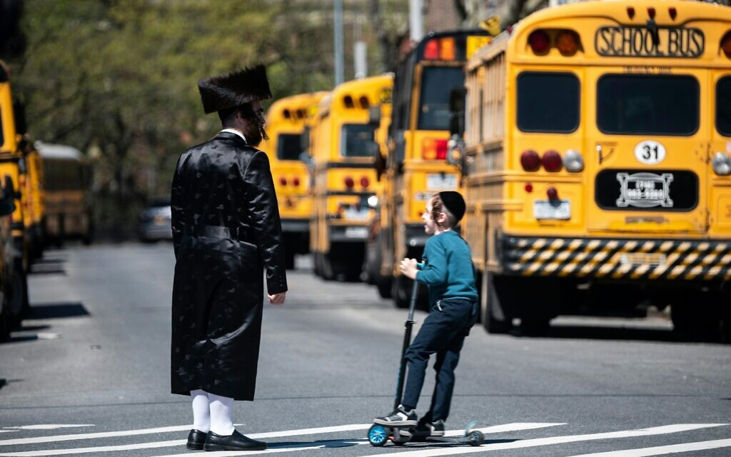 A Jewish man and a child stand on a street in the Williamsburg neighborhood of Brooklyn, April 24, 2019. (Johannes Eisele/AFP via Getty Images/ via JTA)