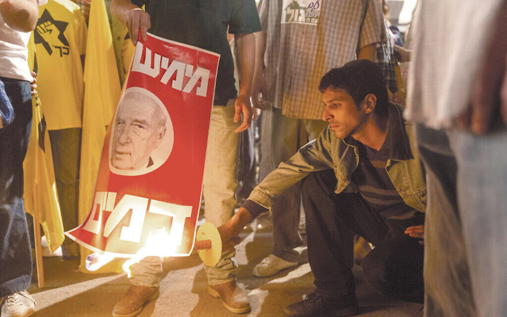 Assassin Yigal Amir, as portrayed by Yehuda Nahari Halev, torches a poster of Israeli Prime Minister Yitzhak Rabin in the film 'Incitement.' (Courtesy of PMKBNC/via JTA)