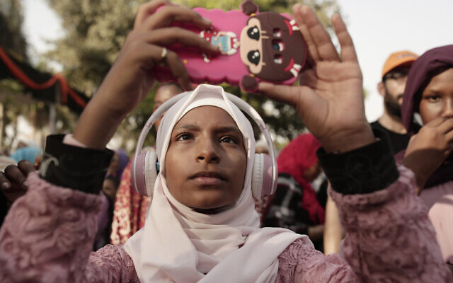 In this June 20, 2019 photo, a teenager films Sudanese dancers on her mobile phone during an event marking the UN's International Refugee Day, in Cairo, Egypt. (AP Photo/Maya Alleruzzo)