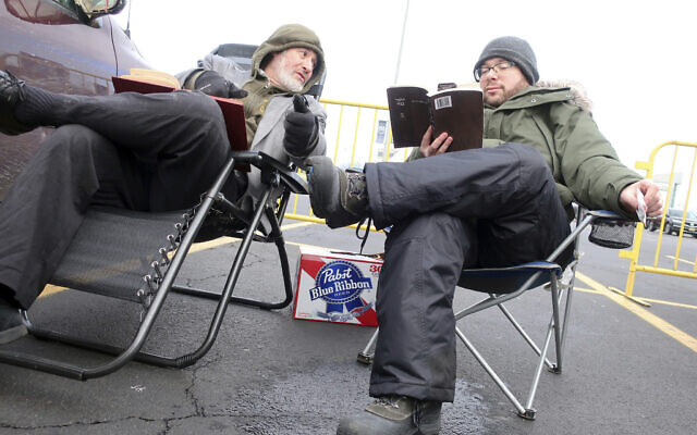 Rabbi Daniel Wasserman of Shaare Torah Congregation in Pittsburgh,, left, studies the Talmud with another man while tailgating in the parking lot of MetLife Stadium, Wednesday, Jan. 1, 2020, in East Rutherford, N.J., at an event called Siyum HaShas, that celebrates the completion of the reading of the Babylonian Talmud, a process that takes 7 1/2 years (AP Photo/Ted Shaffrey)