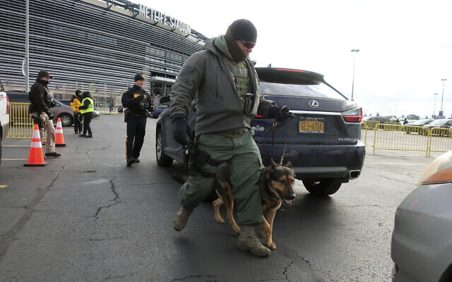 A law enforcement with a dog inspects vehicles parking at MetLife Stadium, Wednesday, Jan. 1, 2020, in East Rutherford, N.J., at an event called Siyum HaShas, that celebrates the completion of the reading of the Babylonian Talmud (AP Photo/Ted Shaffrey)
