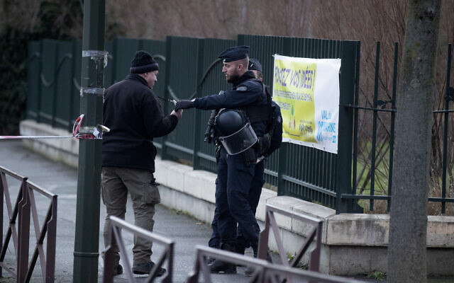 A riot police officer checks a badge after a man attacked passerby January 3, 2020 in Villejuif, south of Paris. (AP Photo/Michel Euler)