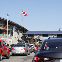 In this Oct. 9, 2019 photo, traffic enters Canada from the United States at the Peace Arch Border Crossing, in Blaine, Wash. The Washington state chapter of the Council on American-Islamic Relations says more than 60 Iranians and Iranian-Americans were detained and questioned at the border crossing over the weekend.  (AP Photo/Elaine Thompson)