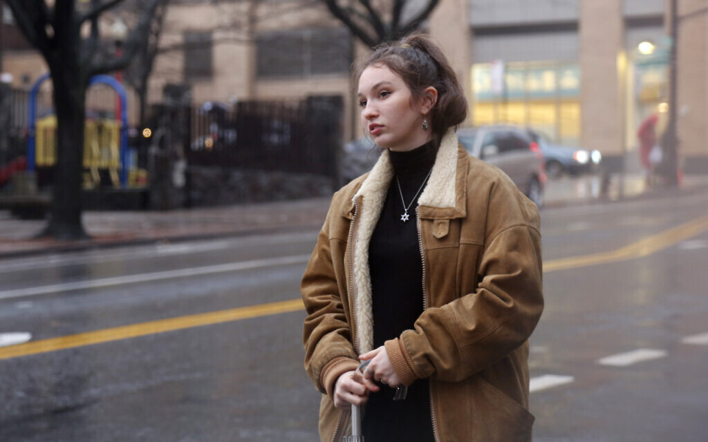 In this December 30, 2019, photo, Shoshana Blum, a 20-year-old junior at City College of New York, waits for a taxi in New York. (AP Photo/Emily Leshner)