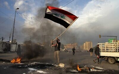 An Iraqi protester waves the national flag while demonstrators set fires to close streets near Baghdad's Tahrir Square during a demonstration against an Iranian missile strike, Wednesday, Jan. 8, 2020. Iran struck back at the United States early Wednesday for killing a top Revolutionary Guard commander, firing a series of ballistic missiles at two military bases in Iraq that house American troops in a major escalation between the two longtime foes. (AP Photo/Khalid Mohammed)